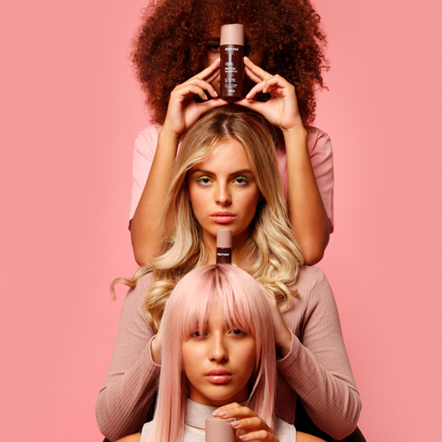 Three girls with different coloured hair are holding each of the three Restora products and facing the camera.