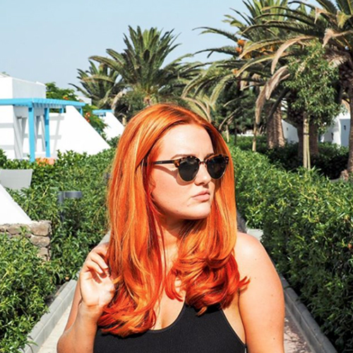 Girl with wavy, red hair is standing in a park and wearing a black string top and sunglasses while looking away from the camera.