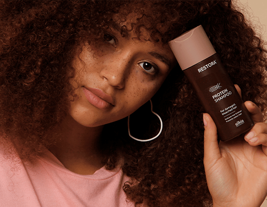 Girl with curly, brown hair holds the Restora Protein Shampoo against her forehead.
