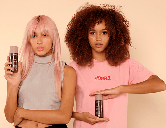 Girl with straight, pink hair holds the Restora Protein Shampoo in her left hand and is standing beside a girl with curly, brown hair who holds the bottle between her hands.
