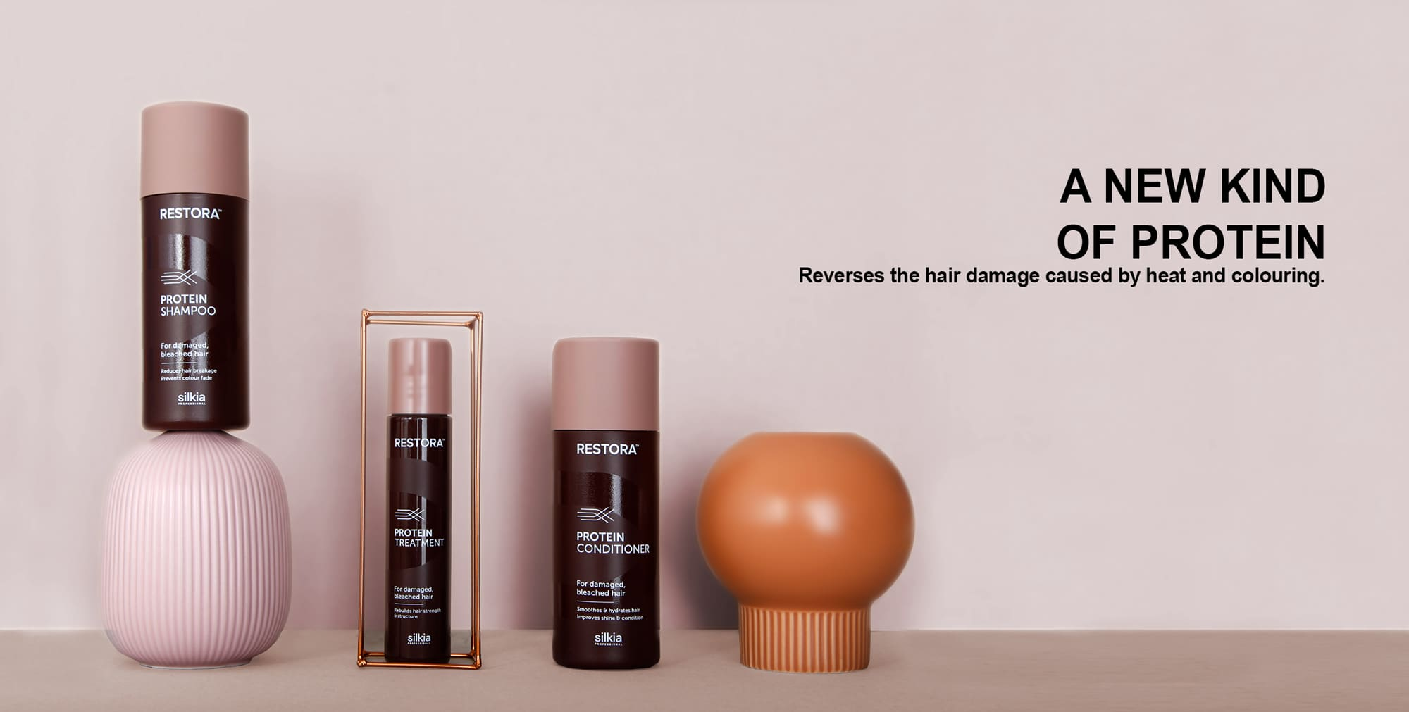 Restora Protein Shampoo, Restora Protein Treatment and Restora Protein Conditioner are shown with props. They reverse the hair damage caused by heat and colouring.