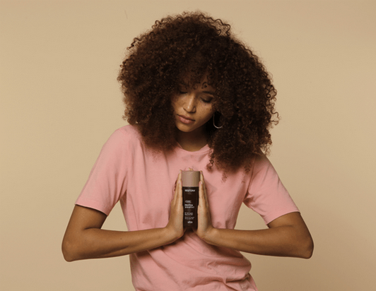 Girl with curly, brown hair holds the Restora Shampoo between her hands.