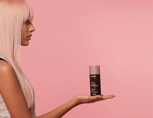 Girl with straight, pink hair is turned to the side and holds the Restora Conditioner in the palm of her right hand.